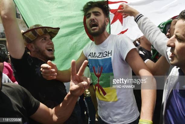 Algerian protesters shout antisystem slogans in front of a national flag during the weekly Friday demonstration in the capital Algiers on June 21...