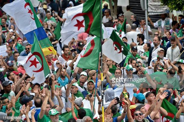 Algerian protesters shout slogans and wave national flags during an antigovernment demonstration outside the the Grand Post Office a key rallying...