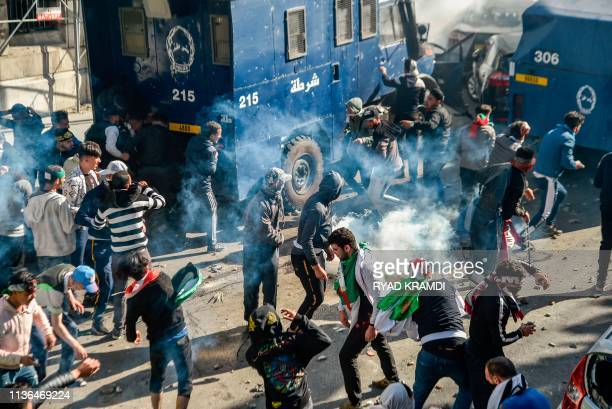 Algerian protesters throw rocks as they clash with riot police during an anti-government demonstration in the capital Algiers on April 12, 2019. -...