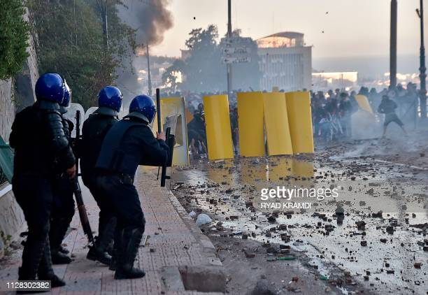 Algerian protesters use makeshift barriers during clashes with security forces amidst protests against ailing President Abdelaziz Bouteflika's bid...