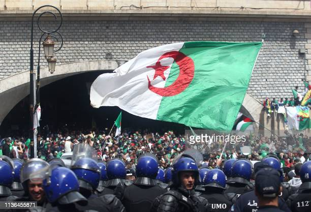 Algerian protesters wave a giant national flag as members of the security forces stand guard during an an antigovernment demonstration in the capital...