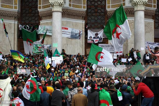Algerian protesters wave national flags as they take part in an antigovernment demonstration in front of La Grande Poste in the centre of the capital...