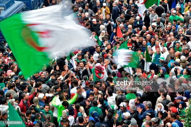 Algerian protesters wave national flags during an anti-government demonstration in the capital Algiers, on December 20, 2019. - Establishment insider...
