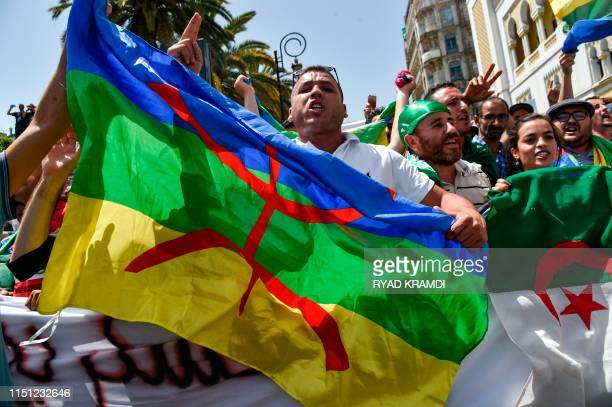 Algerian protesters wave the Amazigh and national flags as they chant slogans during the weekly Friday demonstration in the capital Algiers on June...