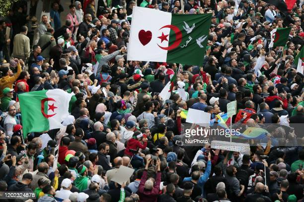 Algerian protesters wave the national flag during their weekly anti-government demonstration in the capital Algiers, on February 21, 2020.