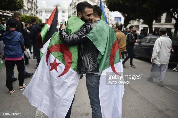 Algerian protesters wrapped in their national flags embrace during an antigovernment demonstration on April 5 2019 in the capital Algiers Algerians...