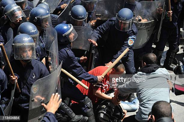 Algerian riot police stand around a man on the ground on May 2 2011 during a demonstration of students demanding political change in the center of...