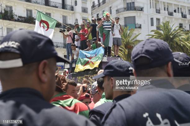 Algerian riot policemen stand guard as protesters take to the streets of Algiers in an antisystem demonstration on June 21 2019 Hundreds of Algerian...