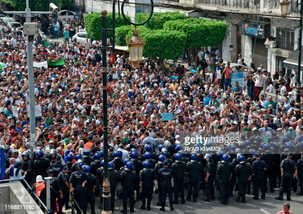 Algerian security forces form a human barrier in front of demonstrators taking part in a rally in the streets of the capital Algiers on September 17,...