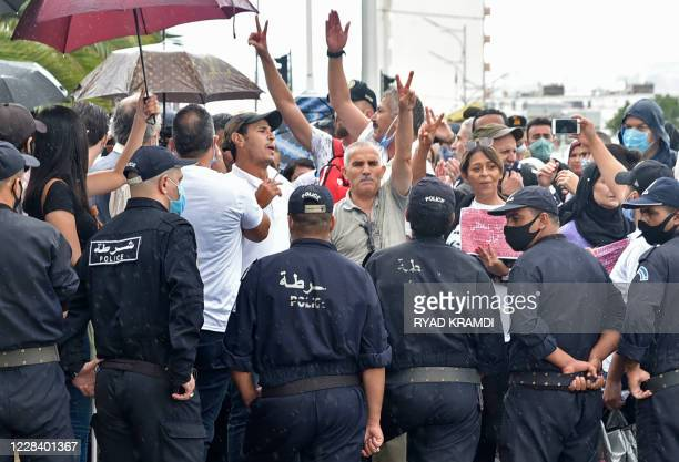 Algerian security forces surround protesters outside a court in Algiers calling for the release from jail of journalist Khaled Drareni, on September...