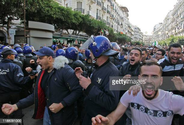 Algerian security forces surround protesters staging an antigovernment demonstration in the capital Algiers on December 12 2019 on the day of the...