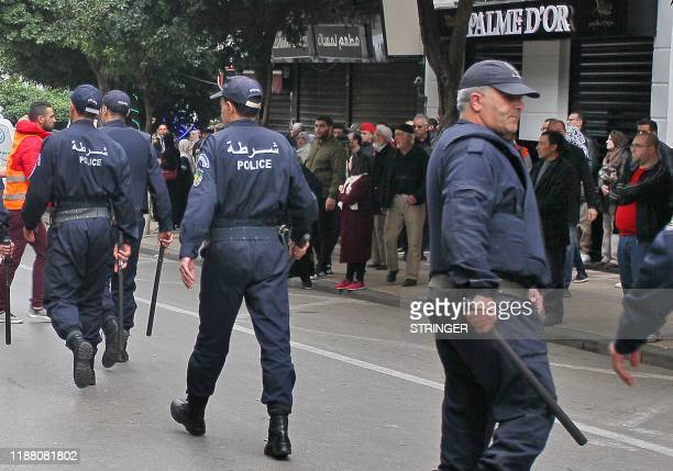 Algerian security forces try to disperse protesters during an antigovernment demonstration in the capital Algiers on December 12 2019 during the...