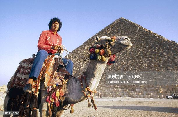 Algerian singer Enrico Macias rides atop a camel during his journey to the Pyramids of Giza Macias was invited by President Anwar Sadat to perform in...