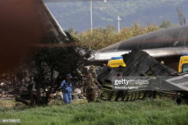 Algerian soldiers and rescuers stand near the wreckage of a military transport aircraft that crashed in Boufarik about 30Kms south the capital...