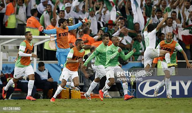 Algerian squad members celebrate at the end of their Group H football match against Russia at the Baixada Arena in Curitiba during the 2014 FIFA...