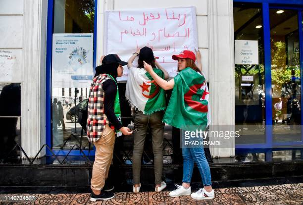 Algerian students draped in national flags hang up a sign reading in Arabic please God accept our fast and prayers and bring down the regime along a...