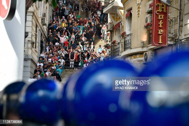 TOPSHOT Algerian students face antiriot policemen as they demonstrate in the capital Algiers on March 5 2019 against ailing President Abdelaziz...