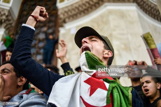TOPSHOT Algerian students shout slogans as they demonstrate with national flags outside La Grande Poste in the centre of the capital Algiers on March...