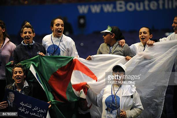 Algerian supporters carry a national flag and proPresident Abdelaziz Bouteflika signs during an election rally on February 12 2009 in Algiers...
