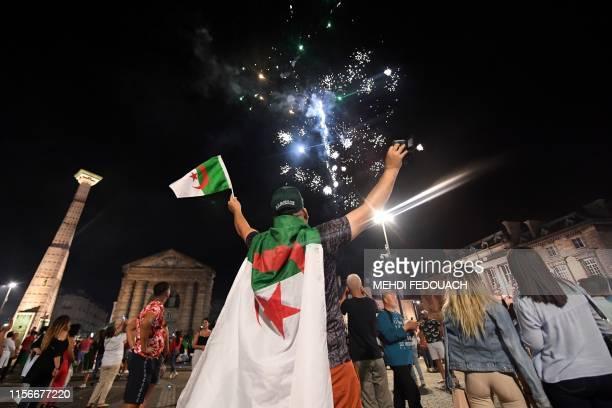 Algerian supporters celebrate as fireworks go off on Place de la Victoire square in Bordeaux, southwestern France, after Algeria won 1-0 the 2019...