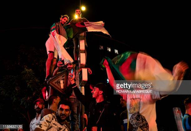 TOPSHOT Algerian supporters celebrate in Guillotiere district in Lyon central eastern France after the victory of their team over Nigeria during the...