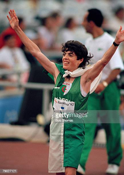 Algerian track athlete Hassiba Boulmerka raises her arms in the air in celebration after finishing in first place to win the gold medal in the final...