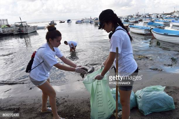 Algerian volunteers collect garbage at the beach of the city of Tamentfoust east of the capital Algiers as part of an initiative titled 'Garbage...