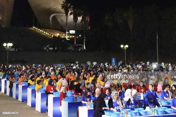 Algerian volunteers try to break the Guinness World Records title for the largest number of people washing dishes at the same time late on June 16 at...