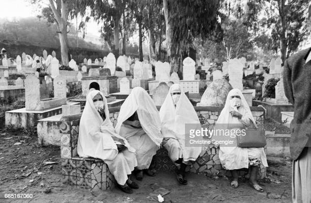 Algerian women in traditional dress sit in a cemetery in Algiers overlooked by Bab elOued Fort