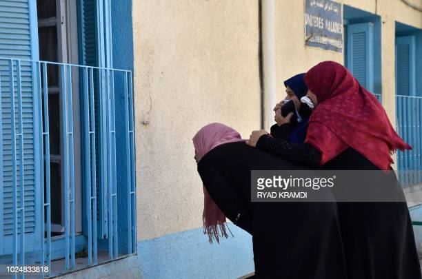 TOPSHOT Algerian women peep into a hopital in the Algerian town of Boufarik as the country faces a cholera outbreak on August 28 2018