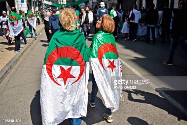 Algerian women protesters draped with the national flag march during a demonstration against ailing President Abdelaziz Bouteflika in the capital...