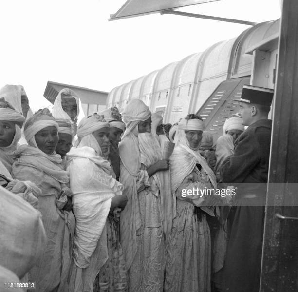Algerian women wait their turn to vote in Keria near Tiaret January 8 under the supervision of a French officer during the Algerian war in the...