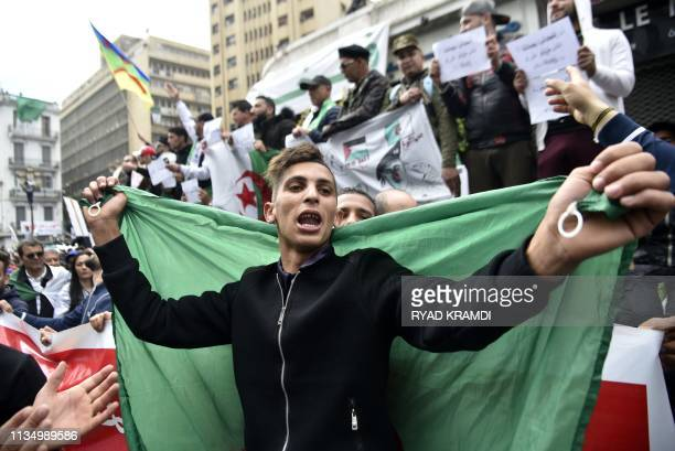 Algerians carry national flags as they take part in an antigovernment demonstration on April 5 2019 in the capital Algiers Algerians were gathered...
