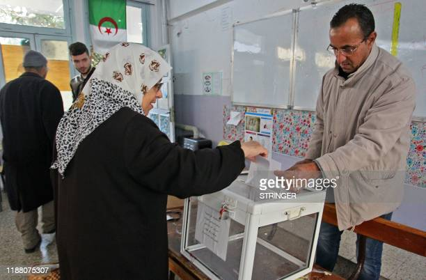 Algerians cast their votes during the presidential election on December 12, 2019 at a polling station in Algiers. - Five candidates are running in...