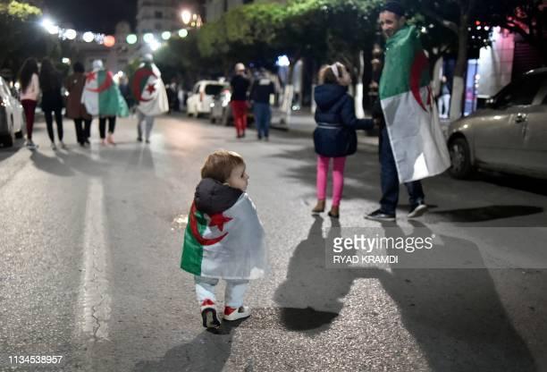 TOPSHOT Algerians celebrate after Algeria's veteran President Abdelaziz Bouteflika informed the Constitutional Council that he is resigning in...