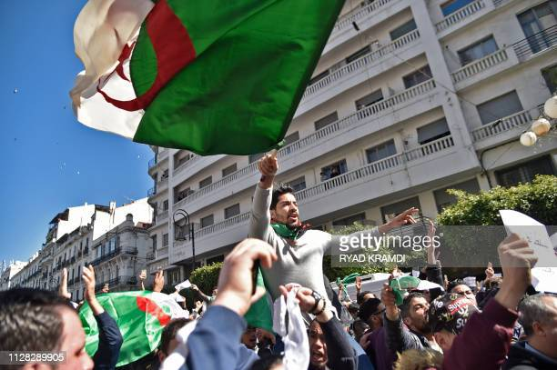 TOPSHOT Algerians chant slogans and wave national flags during a protest rally against ailing President Abdelaziz Bouteflika's bid for a fifth term...
