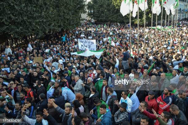 Algerians chant slogans and wave national flags during a protest rally against ailing President Abdelaziz Bouteflika's bid for a fifth term in power...