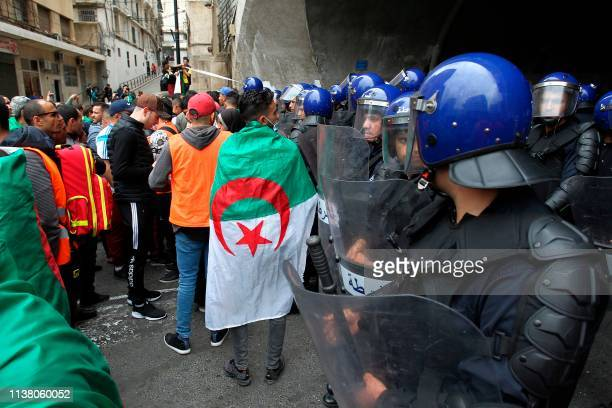 Algerians draped in national flags are surrounded by riot police during an anti government demonstration in the capital Algiers on April 19 2019...