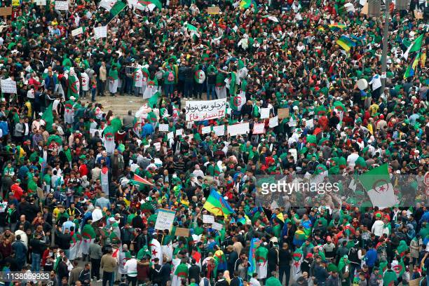 Algerians draped in national flags hold banners and chant slogans during an anti government demonstration in the capital Algiers on April 19 2019...