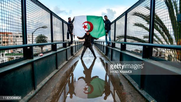 Algerians draped in the national flag take part in a demonstration against ailing President Abdelaziz Bouteflika in the capital Algiers on March 22,...