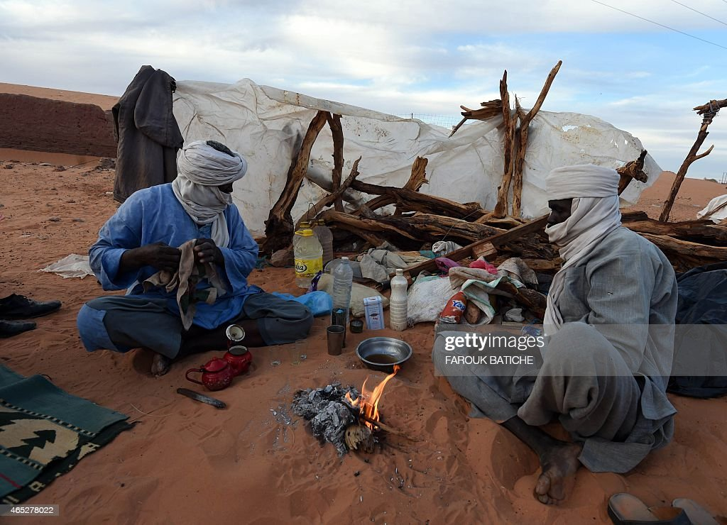 Algerians gather around a fire in the Sahara desert village of In-Salah, south Algeria, on March 5, 2015, following a demonstration against the exploration of shale gas. Anti-shale gas demonstrations have increased in the cities of the Algerian Sahara since late December, when Algerian oil company Sonatrach announced it had successfully completed its first pilot drilling in the In-Salah region. Sonatrach announced in early February that its exploratory drilling for shale gas using hydraulic fracturing would continue despite mounting hostility among people living nearby.