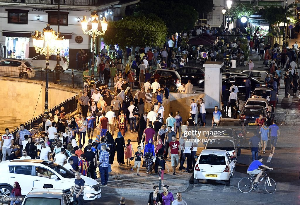 Algerians gather outside Algiers' Grand Post Office during the Muslim holy fasting month of Ramadan on July 12, 2015. During Ramadan the Algerian capital comes alive with animation largely subsidized by the government to prevent the young from becoming strongly influenced by the Imams in this pious period.