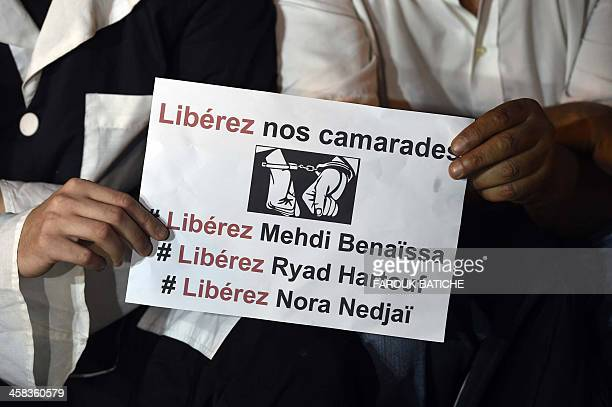 Algerians hold a placard that reads in French 'Free our comrades' during a demonstration by artists and journalists outside the National Theatre in...