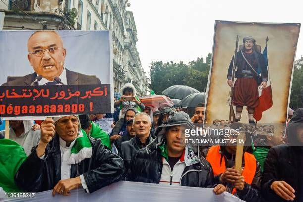 Algerians hold up signs depicting former prime minister Ahmed Ouyahia dressed as a Zouave alongside another showing current PM Noureddine Bedoui with...