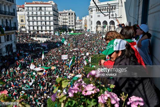 Algerians look down from a balcony upon protesters gathering during a mass demonstration against ailing President Abdelaziz Bouteflika in the capital...