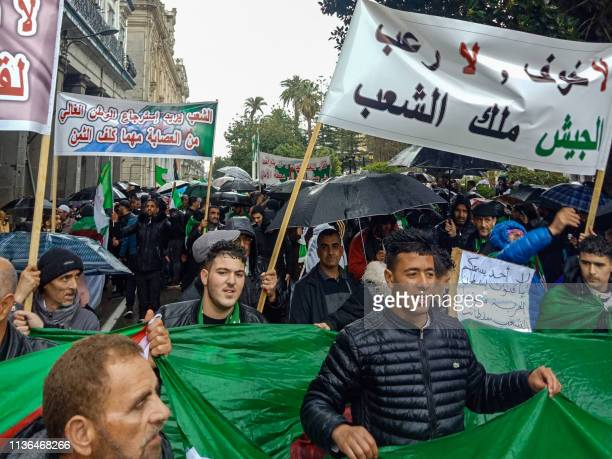 Algerians march with a banner reading in Arabic no fear no terror the army belongs to the people as they take part in an antigovernment demonstration...