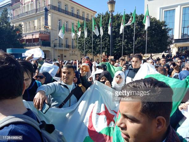 Algerians march with a national flag during a protest rally against their ailing president's bid for a fifth term in power in the northeastern city...