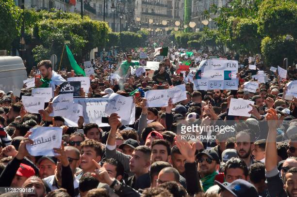 TOPSHOT Algerians march with protest sings reading peaceful and leave means leave in Arabic during a rally against ailing President Abdelaziz...
