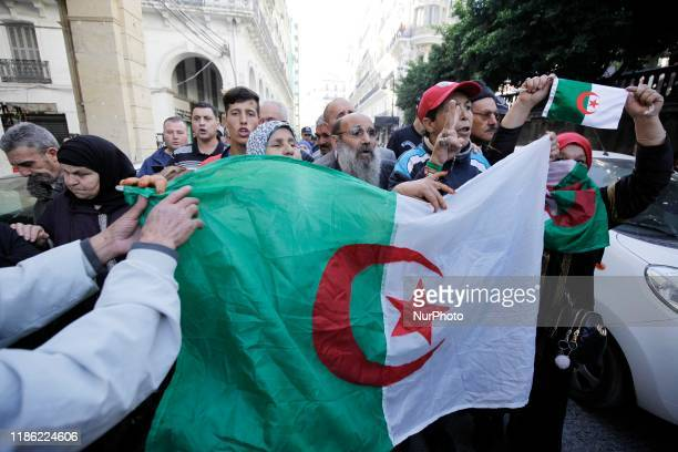 Algerians raise a sign demanding justice, December 2 at the main entrance of the court of Sidi M'hamed, in the Algerian capital, in anticipation of...