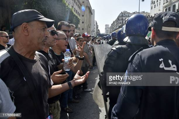 Algerians shout antigovernment slogans during a protest near the parliament building in central Algeirs on October 13 2019 against the military's...